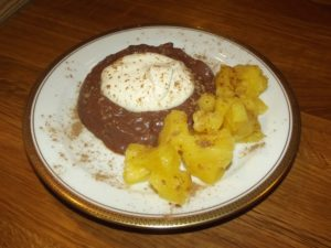 Schokoladenpudding mit Sahne und karamellisierter Ananas.