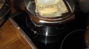 Den Teig mit der Spätzlereibe in kochendes Salzwasser reiben.