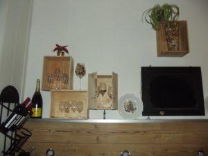 Die Weinkisten werden miteinander verschraubt und versetzt an die Wand montiert. Der Kelch in der Mitte ist mit Korken und einer Lichterkette gefüllt. Rechts an der Kiste befinden sich Türen, die aus einem Weinkisten-Deckel entstanden sind. Dafür müssen auf beiden Seiten zwei kleine Scharniere angebracht werden.