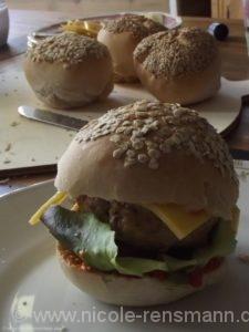 Fischburger mit Käse, Salat und Gurke